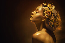 Portrait Closeup Beauty Fantasy Woman, Face In Gold Paint. Golden Shiny Skin. Fashion Model Girl, Image Goddess. Glamorous Crown, Wreath Roses, Jewellery Accessories. Professional Metallic Makeup