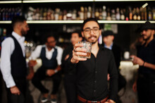 Stylish Arab Man Against Group Of Handsome Retro Well-dressed Guys Gangsters Spend Time At Club, Drinking On Bar Counter. Multiethnic Male Bachelor Mafia Party In Restaurant.