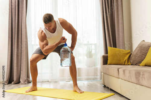 Photo Young athletic man using big bottle of water for home workout