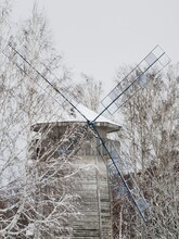 Windmill Among The Trees. Winter Landscape, The Village Is Covered With Snow