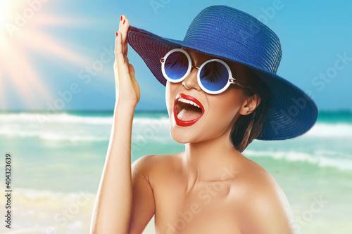 Obraz Beautiful woman wearing blue hat and sunglasses enjoying beach vacation - fototapety do salonu