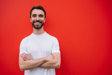 Young Handsome Man With Arms Crossed Wearing Casual T-shirt Isolated On Red Background. Portrait Of Stylish Bearded Guy With Happy Emotional Face Looking At Camera