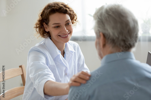 Fotografiet Happy young 30s beautiful physician doctor nurse supporting elderly mature retired patient, sharing good news about health test results, feeling satisfied with disease treatment at checkup meeting
