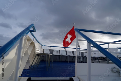 Fotografia, Obraz Swiss federal flag blowing in the wind over Lake Zurich on a lake cruise ship