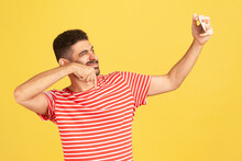 Cheerful Smiling Man Blogger With Beard In Striped T-shirt Winking Asking To Subscribe Looking At Smartphone Camera, Making Selfie Or Recording Video. Indoor Studio Shot Isolated On Yellow Background