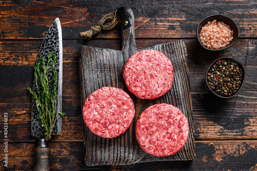 Fototapeta Raw steak burgers patties with ground beef and thyme on a wooden cutting board. Dark Wooden background. Top view obraz