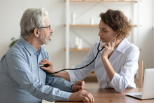 Focused Young Female Cardiologist Or General Practitioner In White Coat Listening Heartbeat Or Elderly Senior Male Patient At Checkup Meeting, Preventing Cardiovascular Disease, Healthcare Concept.