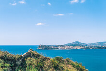 View In The Gulf Of Naples From Monte Di Procida With The Islands Of Procida And Ischia In The Background And Vegetation In The Foreground, Under A Blue Sky With Cloud