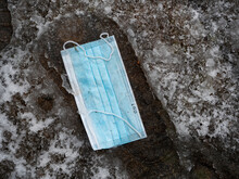 CLOSE UP: Light Blue Surgical Masks Falls Into A Footprint In The Snow Slush.