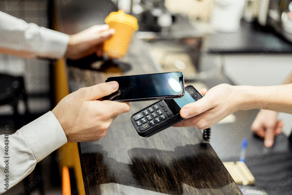 Fototapeta NFC payment phone next to the terminal. a man pays for a purchase in a cafe restaurant with him.