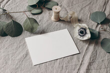 Wedding Stationery Mock-up Scene. Blank Greeting Card On Linen Tablecloth Background With White Anemone Flower, Eucalyptus Tree Branches And Silk Ribbon. Feminine Still Life Composition. High Angle.