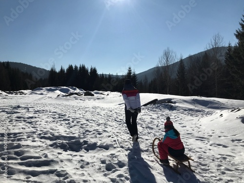 Obraz Mother Pulling Sled With Daughter On Snow Covered Field - fototapety do salonu