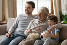 Overjoyed Three Generations Of Men Relax On Sofa In Living Room Watch Football Match Eat Popcorn. Happy Boy With Young Father And Elderly Grandfather Have Fun Rest At Home On Family Weekend Together.