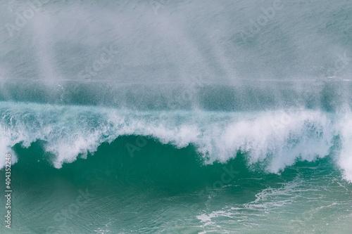 Fototapeta Windswept wave as the spray is carried away