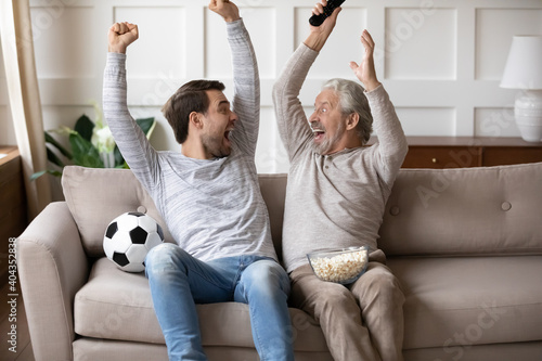 Slika na platnu Excited millennial Caucasian man with elderly father feel euphoric celebrate win watch football game on TV together