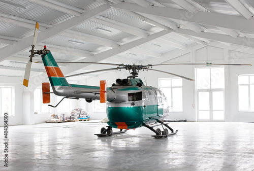 Fotografia Green and silver, helicopter in light hangar against large windows