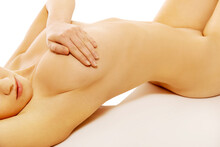 Midsection Of Naked Woman Lying Over White Background
