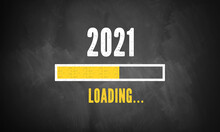 Text 2021 LOADING With A Loading Bar Indicator On A Blackboard