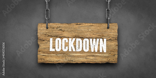 Obraz .wooden sign on chains with message LOCKDOWN in front of concrete background - fototapety do salonu