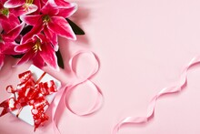 8 March, International Women's Day. Figure Eight Of Pink Ribbon With Lilly Flower And Gift Box On Pink Background. Space For Text. Flat Lay.