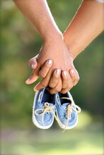 Close-up Of Cropped Couple Holdings With Baby Booties
