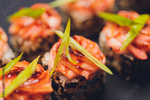 Fototapeta Maki Sushi Rolls with salmon on black stone on dark background. With ginger and wasabi. Sushi menu. Japanese food. Closeup of delicious japanese food with sushi roll. Horizontal photo. obraz