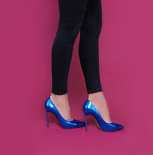 Low Section Of Woman Wearing Blue Stiletto Standing Against Pink Background