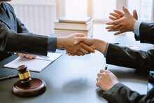 Man Lawyer Shaking Hands With His Clients In The Office.