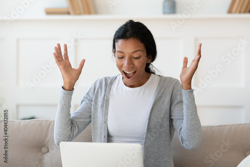 Emotional young happy african ethnicity woman looking at laptop screen, celebrating getting email with online lottery win, dream job offer or bank loan approvement, personal success good luck concept Fototapeta