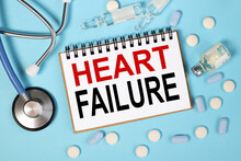 Heart Failure, Text On White Notepad Paper On Blue Background. Stethoscope And Pills In The Picture