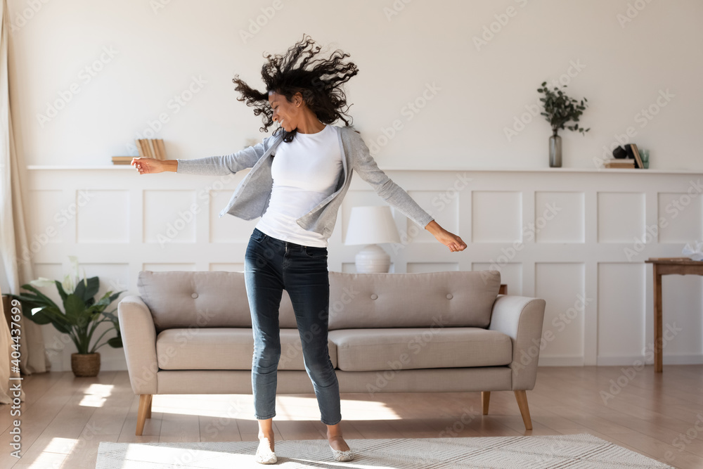 Fototapeta Full length young african ethnicity multiracial woman in casual wear dancing to favorite energetic audio music, having fun alone in living room, enjoying active domestic hobby pastime, feeling freedom
