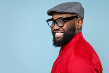 Side View Of Smiling Handsome Young Bearded African American Man 20s Wearing Casual Red Shirt Eyeglasses Cap Standing And Looking Camera Isolated On Pastel Blue Color Wall Background Studio Portrait.