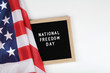 black letter board with text national freedom day and American flag on white background . top view flat lay copy space