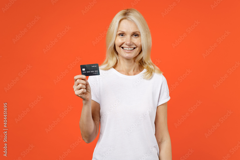 Fototapeta Smiling elderly gray-haired blonde woman lady 40s 50s years old in white basic t-shirt standing hold in hand credit bank card looking camera isolated on bright orange color background studio portrait.