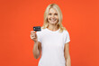Smiling elderly gray-haired blonde woman lady 40s 50s years old in white basic t-shirt standing hold in hand credit bank card looking camera isolated on bright orange color background studio portrait.