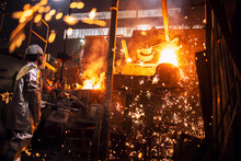 Foundry Worker Controlling Process Of Melting Iron In Furnace. Burning Liquid Steel Pouring And Sparks Flying All Around. Metallurgy And Heavy Industry.