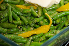 Detail Of Fresh Organic Green Beans Mixed With Yellow Spicy Peperoni In Glass Tray Ready For Cooking In Oven