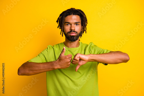 Obraz Photo of serious dark skin guy show thumb up thumb down symbol isolated over vivid yellow color background - fototapety do salonu