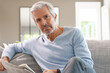 Attractive senior man relaxing at home reading newspaper