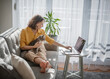Casual woman in yellow shirt working on laptop with her cat on sofa, sitting together in modern room with window ang green plan