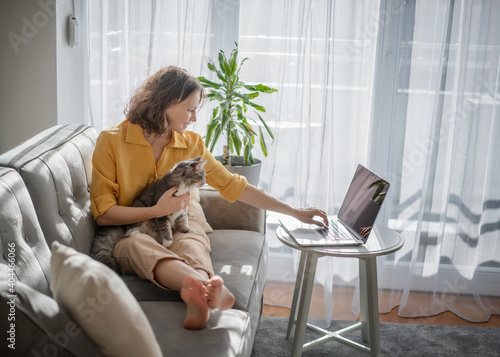 Obraz Casual woman in yellow shirt working on laptop with her cat on sofa, sitting together in modern room with window ang green plan - fototapety do salonu
