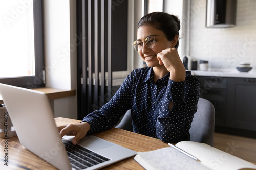 Fotomural Happy millennial Indian woman in glasses sit at desk in home office look at laptop screen working online