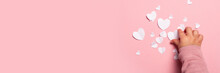 Child's Hand Takes A Valentine Card From Paper On A Pink Background. Composition Valentine's Day. Banner. Flat Lay, Top View