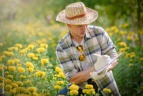 Papel de parede Young Man Writing On Document By Flowers On Farm