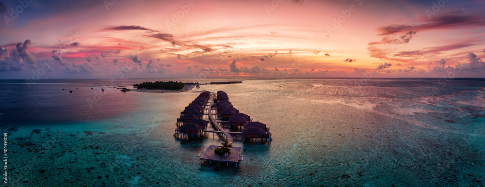 Fototapeta Aerial panorama of a tropical paradise island in the Maldives, Indian Ocean, with water lodges over the turquoise reef during sunset time