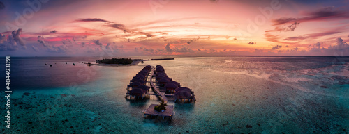 Obraz Aerial panorama of a tropical paradise island in the Maldives, Indian Ocean, with water lodges over the turquoise reef during sunset time - fototapety do salonu