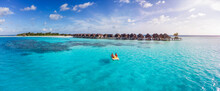 Aerial View Of A Happy Family Enjoying A Pedalo Boat Ride Over The Turquoise Ocean Of The Maldives Islands