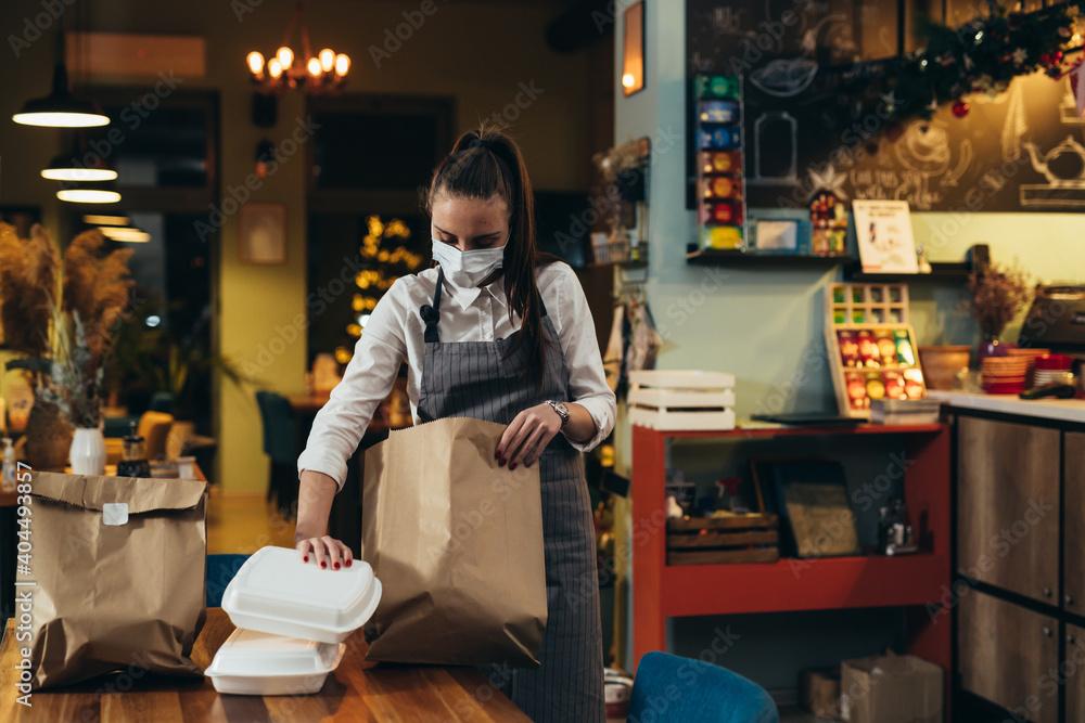 Fototapeta woman waitress preparing take away food in restaurant