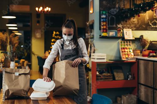 Obraz woman waitress preparing take away food in restaurant - fototapety do salonu