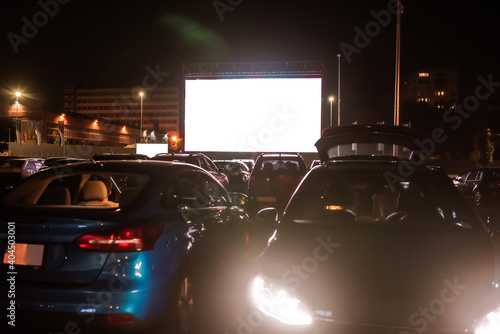 Obraz The best place to go. Many cars parked in front of a big white screen to watch movies or films sitting inside the car at drive in cinema in the evening - fototapety do salonu